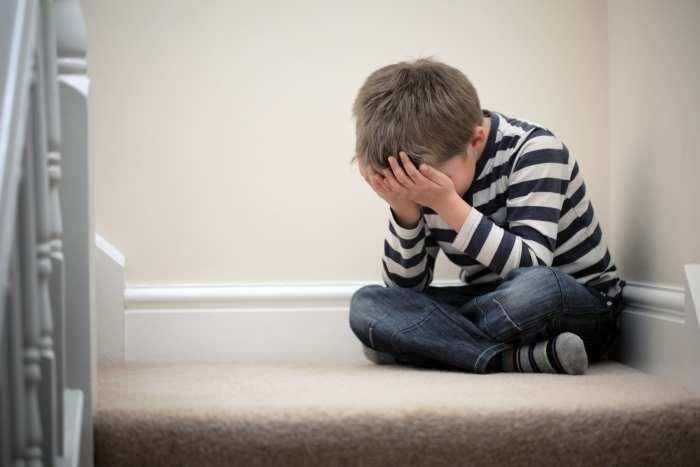 Verzweifelt aussehender Junge sitzt auf einer Bank neben einer leeren Schaukel